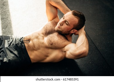 Muscular man exercising doing sit up exercise. Athlete with six pack, white male, no shirt
