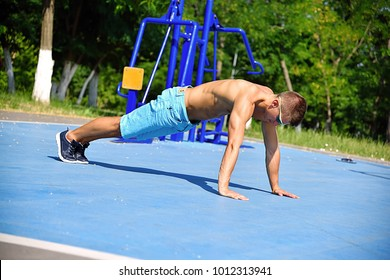 Muscular Man Exercising Push-ups On Playground Outdoors. Crossfit Concept