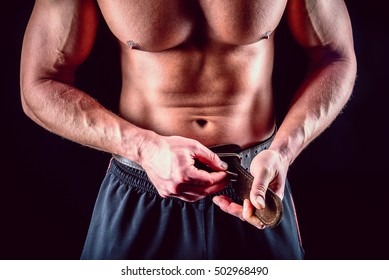Muscular man fasten lifting belt over dark background