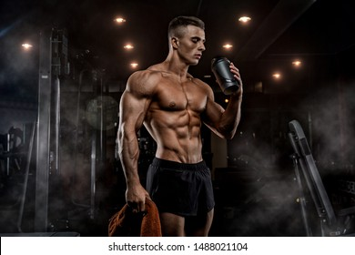 Muscular man in gym with shaker. Strong male abs, working out