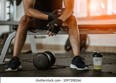 Muscular man at gym taking a break from workout sitting beside the bottle of mineral salt and dumbbells .