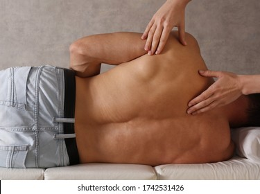 Muscular Man having Chiropractic Back Adjustment / Physiotherapy treatment . Back pain relief, Injury Rehabilitation