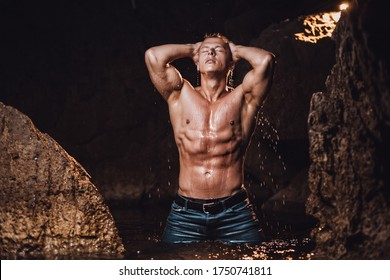 muscular man having shower and splashing water outdoors in sea. Handsome man wearing wet jeans outdoors.