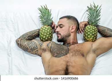 muscular man hold pineapple fruit on biceps. brutal sportsman relax in bed. steroids. sexy ab of tattoo man diet. male health. muscular macho man with athletic body. exotic fruit healthy food vitamin