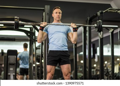 Muscular man holding barbell at the gym.