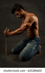 Muscular Man holding a dagger knife while on his knees