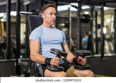 Muscular man holding dumbbell at the gym.