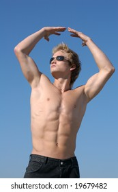 Muscular man holding his hands up in a blue sky