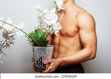 Muscular man holding orchid in a hands on light background