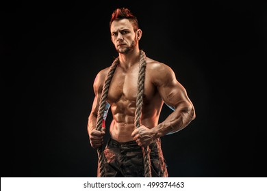 Muscular man holding rope and posing with serious face on the black background