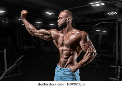 Muscular man in jeans poses in the gym. Sports, bodybuilding, powerlifting concept. Mixed media