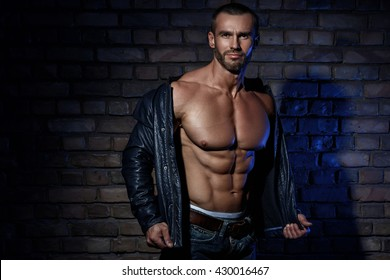 Muscular man in leather jacket against brick wall