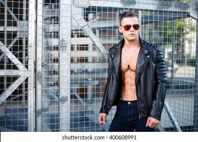 Muscular man in leather jacket and sunglasses. Industrial portrait.