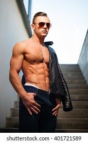 Muscular man in leather jacket and sunglasses on stairs.