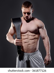 Muscular man in with lifting belt posing over dark background