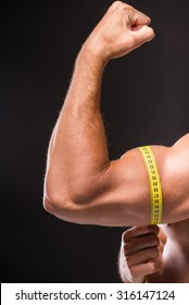 Muscular man is measuring arm, bicep and tricep with tape measure, close-up of arm on dark background.