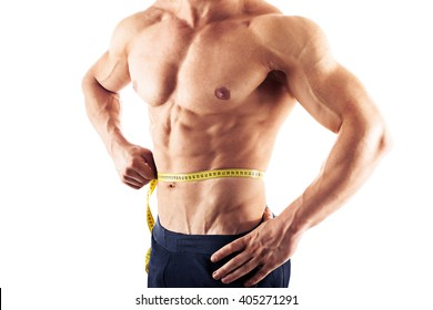Muscular man measuring his waistline