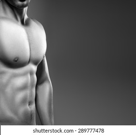 Muscular man with naked chest posing in studio. Photo made in black and white