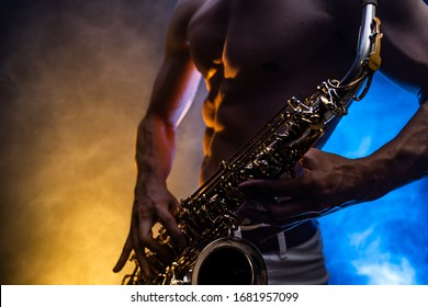 Muscular man with naked torso playing on saxophone with smoked colorful background