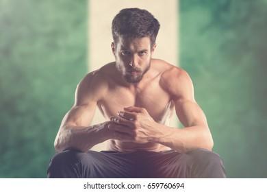 Muscular man with Nigeria Flag behind