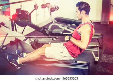 Muscular man on rowing machine at gym