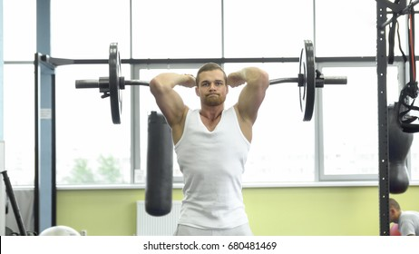 Muscular Man On Strength Training In The Gym Athlete Makes Triceps Exercise With A Barbell