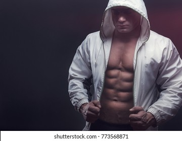 Muscular man with open white jacket revealing abs on the black background. Sexy guy. Sport concept image