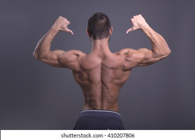 muscular man with perfect body is demonstrating its rear without a shirt on a dark background