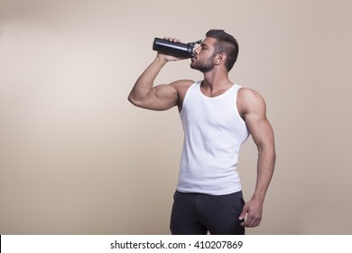 muscular man with perfect body drinking protein shake on a light background