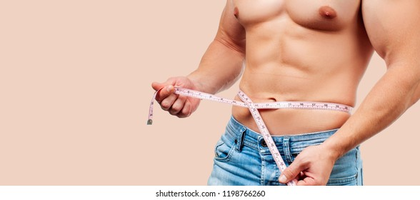 Muscular man with perfect body measuring his waist on pastel background.