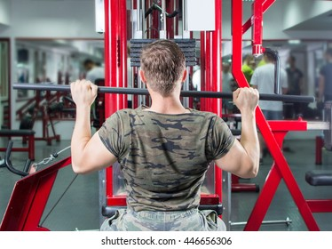 Muscular man performing lat pull down at the gym