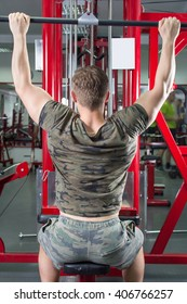 Muscular man performing lat pulldown at the gym