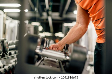 Muscular man is picking up weights from stand, preparing his training