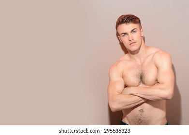 Muscular man. Portrait of young attractive topless man with crossed arms against isolated background.