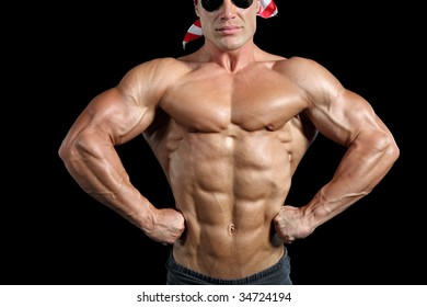 Muscular man posing against black background