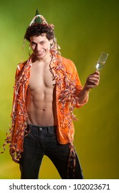 muscular man posing with glass and confetti in studio