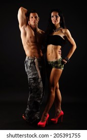 Muscular man posing with his girlfriend on dark background