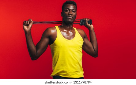Muscular man posing with jumping rope on red background. African fitness model with skipping rope.