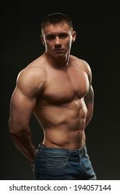 Muscular man posing in studio over black background