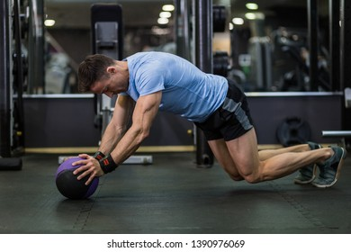 Muscular man practicing plank exercise using a ball at the gym.