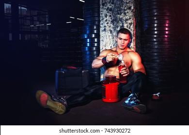 Muscular man preparing protein cocktail in shaker in gym. Bodybuilder holding bottle blender. Photo with toning