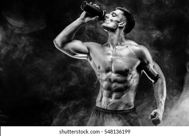 Muscular man with protein drink in shaker over dark smoke background