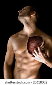 A muscular man pulling his chest skin away showing the pectoral muscle underneath