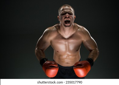 Muscular man  in red gloves screaming and roar over black background