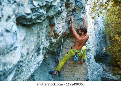 muscular man rock climber in bright yellow pants climbing the challenging route on the cliff in forest. strong bearded rock climber climbs on a rocky limestone wall, side view. sport and active