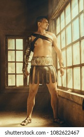 The muscular man in Roman armor. gladiator in armour. concept of masculinity, determination, strength
