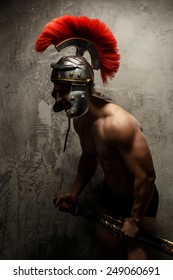 The muscular man in Roman armor holding sword.