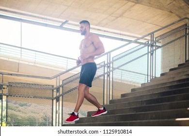 Muscular man running down the stairs by day