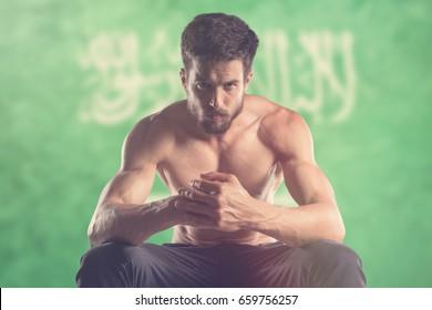 Muscular man with Saudi Arabia Flag behind