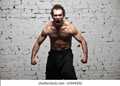 muscular man screaming and roar at brick background